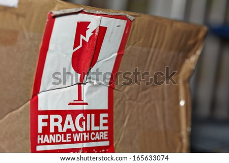 Fragile Handle With Care Sign On A Damaged Package - stock photo