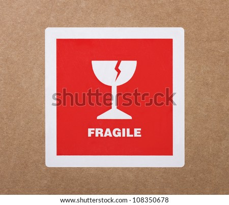 Fragile sticker at the cardboard package - stock photo