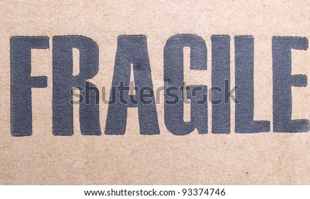 Fragile warning sign label tag on a cardboard box packet parcel for mail post shipping - stock photo