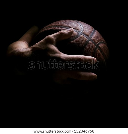Fragment of a basketball ball in a hand of the basketball player - stock photo