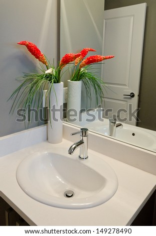 Fragment of a bathroom, washroom with washbasin (sink) and the vase as a decorative element on the counter. Interior design. Vertical. - stock photo