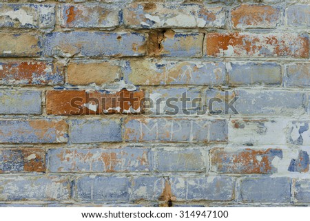 Fragment of a brick wall with cracks, scratches and attritions - stock photo