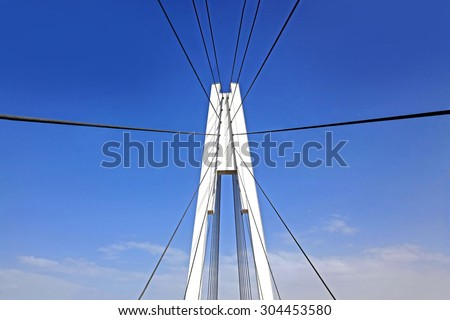 fragment of a cable stayed bridge on the sky background - stock photo