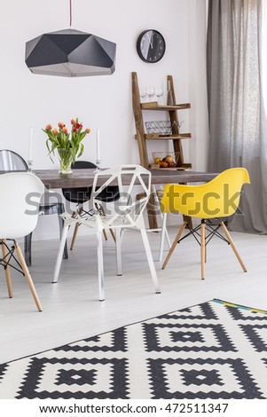 Fragment of a dining room in a modern apartment, with a set of designer chairs, a ladder rack and a large table