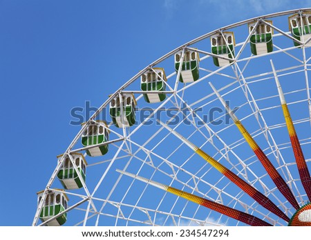Fragment of a ferris wheel against clear blue sky - stock photo