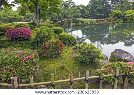 Fragment of a Japanese garden with bamboo fence decorative bushes with pink flowers and lake in background - stock photo