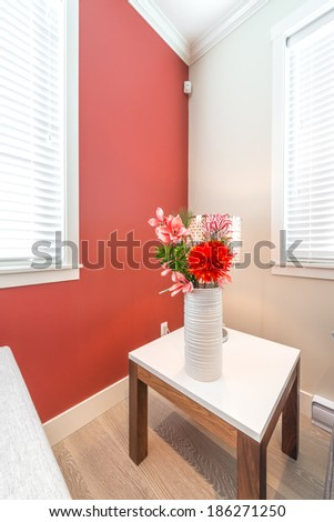 Fragment of a luxury living suite. Nicely decorated modern family, living room with decorative vase with some flowers on the coffee table and red colored room. Interior design. Vertical.