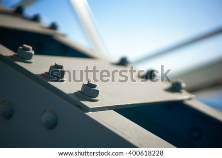 Fragment of a metal construction with bolts and nuts - stock photo