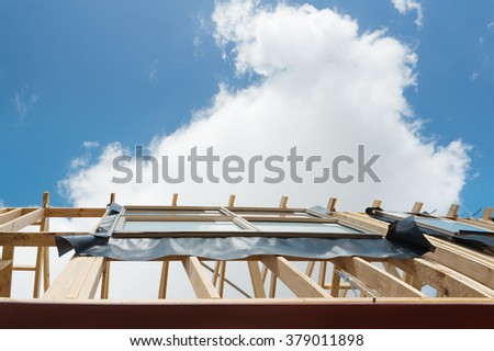 Fragment of a new residential construction home framing against a blue sky. - stock photo