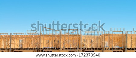 Fragment of a new residential construction home framing against a blue sky as copy space - stock photo