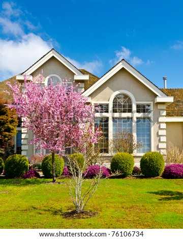 Fragment of a nice house with blossom cherry tree in front in Vancouver, Canada. - stock photo