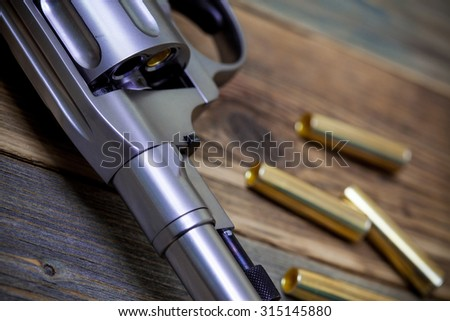 fragment of a revolver Nagan with one bullet in the drum for game Russian roulette - stock photo