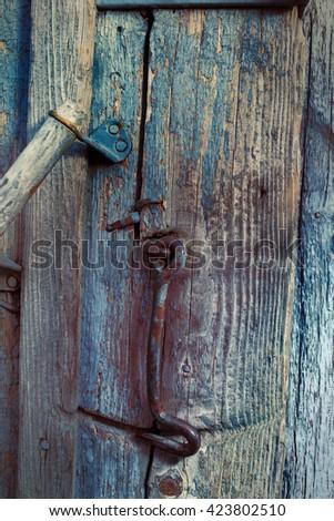 Fragment of a rural wooden door with a metal hook. - stock photo