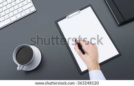 Fragment of a workplace with blank notepad and a cup of black coffee to the left, datebook to the right, hand making notes with a pen. Concept of work