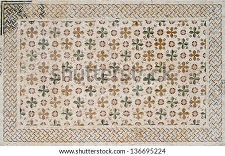 Fragment of an ancient  floor mosaic carpet. Colorful small tiles, unusual geometric image, ornament of spectacularly colored cross-shaped flowers leaves and buds.Church crypt. Israel  - stock photo