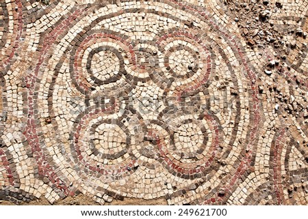 Fragment of an ancient  floor mosaic. Colorful small tiles, unusual geometric image, oval forms in ornament. The ruins of the temple ~ 4th century. Phoenician settlement Shikmona. Israel  - stock photo