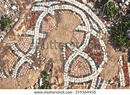 Fragment of an ancient  floor mosaic. Colorful small tiles, unusual geometric image, oval forms in ornament. The ruins of the temple ~ 4th century. Phoenician settlement Shikmona. Israel