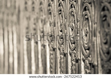 fragment of an ancient pig-iron fence with the abstract forged pattern of beige color