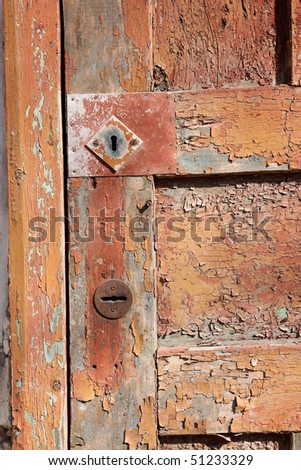 Fragment of an old, shabby brown door, two keyholes