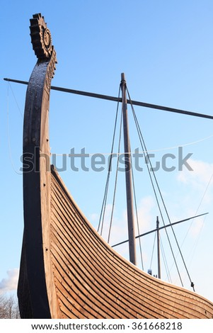 Fragment of ancient Viking ship named Drakkar against blue sky - stock photo