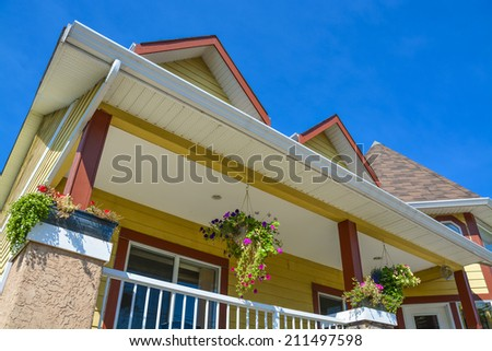 Fragment of beautiful residential house on blue sky background. Bed and breakfast hotel in British Columbia, Canada.  - stock photo