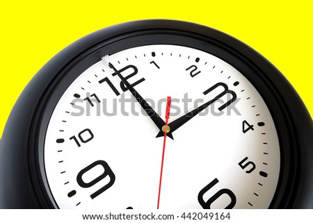 Fragment of big round wall clock, with a black rim isolated on white background close-up and arrows showing three o'clock isolated on yellow close-up - stock photo