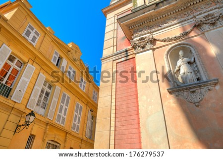 Fragment of catholic church and yellow building under blue sky in town of Menton, France.