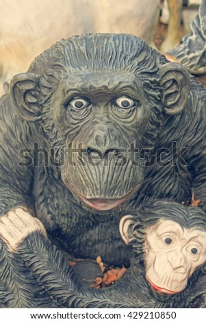 Fragment of ceramic sculpture of a gorilla with a baby. Toned - stock photo