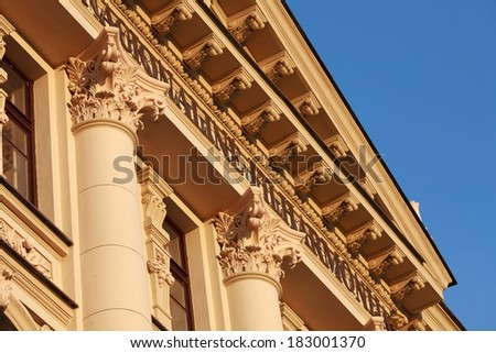 Fragment of classic or neoclassic building with columns and fine capitals, illuminated with warm summer sunlight, blue sky visible. - stock photo