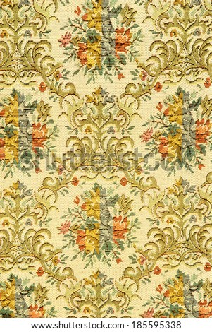 Fragment of colorful retro tapestry textile pattern with handmade floral ornament and flowers as background.