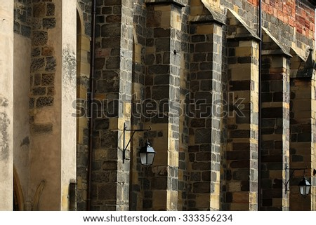 Fragment of columned facade of typical time-worn gray stone house with some old style street-lamps closeup on seamless background, horizontal picture - stock photo