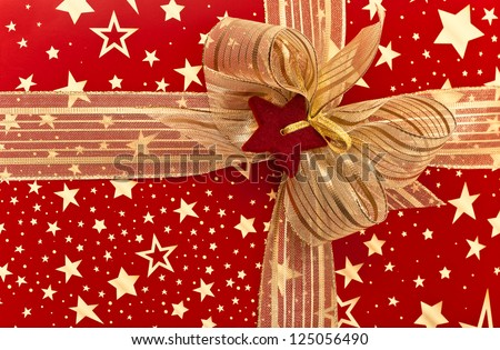 Fragment of festive box with golden ribbon - stock photo