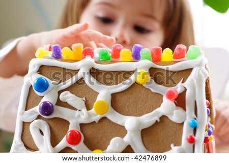 Fragment of gingerbread house roof dotted with colorful candy and little girl face on background - stock photo