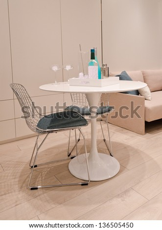 Fragment of Interior design of a modern living room with a table and two chairs and a sofa - stock photo
