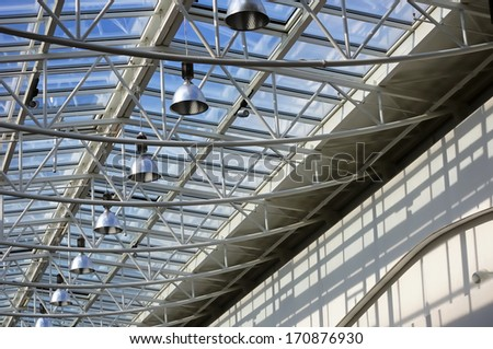 Fragment of modern building with roof made of glass and metal with row of lamps against blue sky background - stock photo