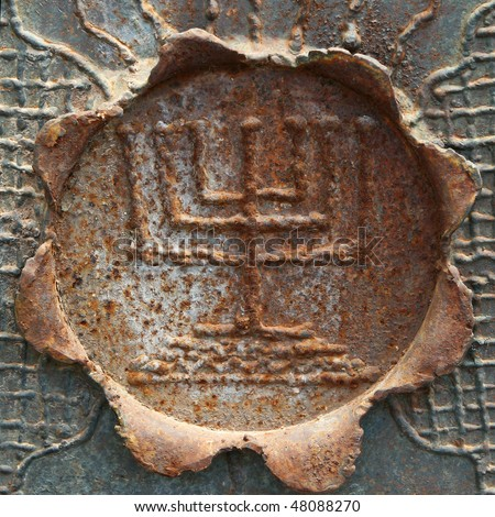 Fragment of old Jerusalem fence with decorative menorah on the rusty metal flower. - stock photo