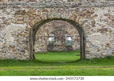 Fragment of  old ruins built with stone bricks  with a gate with  in the center giving view across the ruins - stock photo