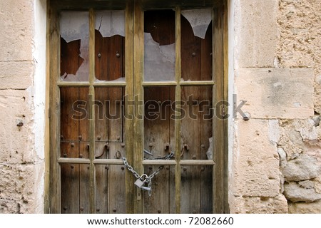 Fragment of old wooden door with glasses of windows broken. Chain and padlock, knockers and nails forged steel and oxidized.  Simple sandstone wall of facade.