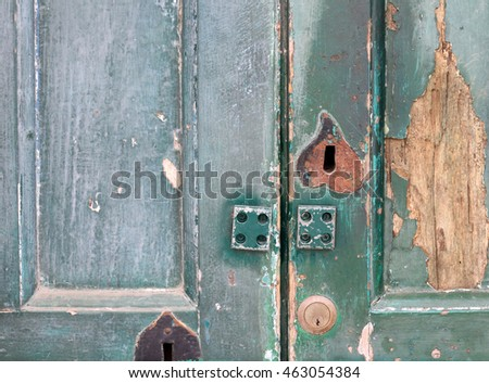 fragment of old wooden door with keyhole and door lock close-up