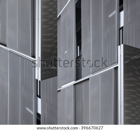 Fragment of paneled latticed metal wall of industrial premises with slightly open windows. Black and white photo of abstract hi-tech architecture detail.
