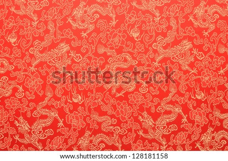 Fragment of red chinese silk with golden dragons and flowers as symbol of Chinese New Year celebration. - stock photo