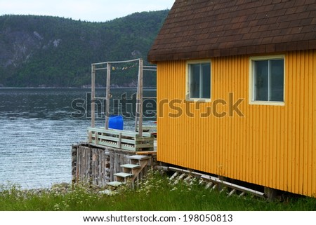 Fragment of rustic yellow cabin by the lake