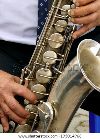 fragment of tenor saxophone with hands of musician - stock photo