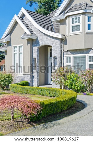 Fragment of the big luxury  home with nicely trimmed bushes at the doorway  in the suburbs of Vancouver, Canada