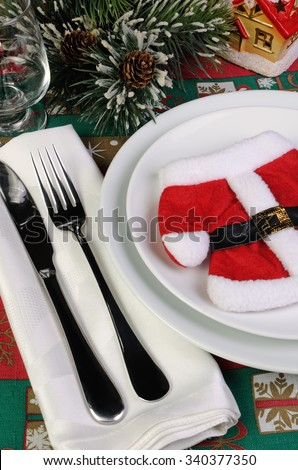 Fragment of the Christmas table serving coat of Santa Claus with cutlery - stock photo