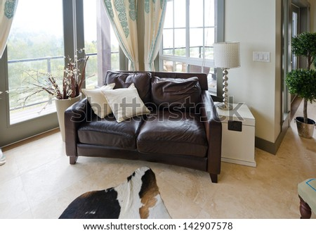 Fragment of the luxury spacious modern living room with the leather sofa. Interior design. - stock photo