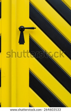 Fragment of the old wooden door painted yellow and black