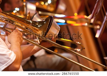 Fragment of the trombone in the hands of a musician in the orchestra - stock photo