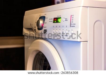 Fragment of the washing machine on a dark background. Control Panel washing machine with luminous indicators. - stock photo