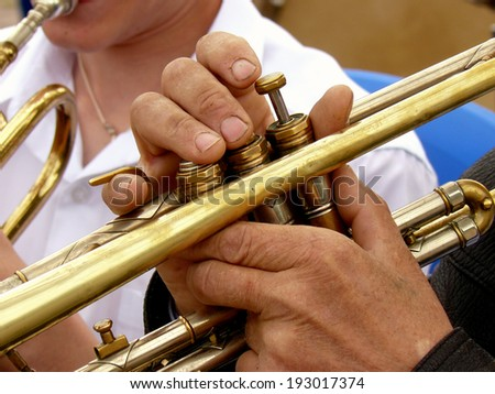 fragment of trumpet with hands of musician - stock photo